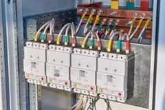 Cuatro disyuntores de poder se fijan en el gabinete eléctrico en línea fotos de archivo