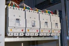 Cuatro disyuntores industriales potentes se fijan en el gabinete eléctrico en línea imágenes de archivo libres de regalías