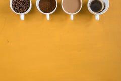 Cuatro diversas tazas en un fondo amarillo fotos de archivo libres de regalías