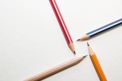 Cuatro diversos colores del lápiz encendido sobre blanco Imagen de archivo libre de regalías
