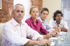 Cuatro empresarios en la sala de reunión imagen de archivo