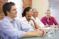 Cuatro empresarios en la sonrisa de la sala de reunión Imagen de archivo libre de regalías