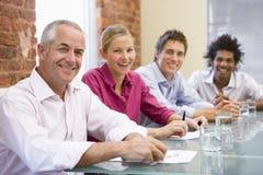 Cuatro empresarios en la sonrisa de la sala de reunión foto de archivo libre de regalías