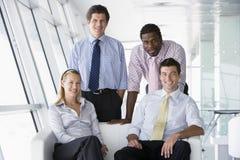 Cuatro empresarios en la sonrisa del pasillo de la oficina Fotografía de archivo libre de regalías