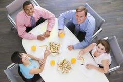 Cuatro empresarios que comen en el vector de la sala de reunión Fotografía de archivo libre de regalías