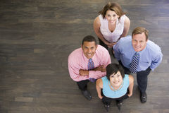 Cuatro empresarios que se colocan dentro sonrientes Fotos de archivo