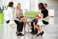 Cuatro empresarios que tienen reunión en oficina moderna Foto de archivo libre de regalías
