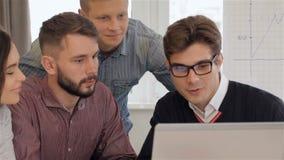 Cuatro encargados creativos jovenes miran el ordenador portátil la oficina almacen de video