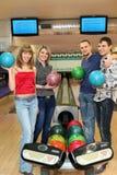 Cuatro estudiantes colocan el bowling de bolo cercano con las bolas Foto de archivo libre de regalías