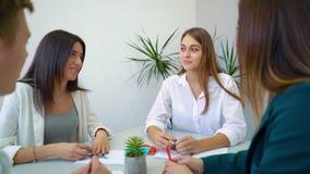 Cuatro estudiantes de la escuela secundaria que se sientan en la tabla y que discuten la asignación del instituto en biblioteca almacen de metraje de vídeo