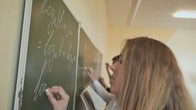 Cuatro estudiantes escriben en las fórmulas matemáticas de la pizarra en la sala de clase Escuela rusa almacen de video
