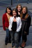 Cuatro estudiantes jovenes que presentan en la calle Imagen de archivo libre de regalías