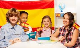 Cuatro estudiantes multiétnicos felices que sostienen banderas Fotos de archivo libres de regalías