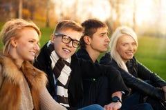 Cuatro estudiantes que se sientan en el parque Imagen de archivo