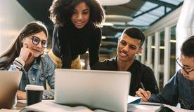 Cuatro estudiantes que usan el ordenador portátil para la investigación en la biblioteca fotos de archivo