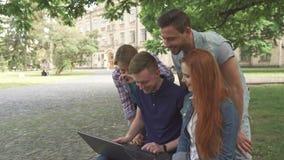 Cuatro estudiantes se ríen de lo que ven en el ordenador portátil en campus almacen de metraje de vídeo