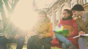 Cuatro estudiantes tienen una discusión que se sienta en el parque cerca de campus metrajes