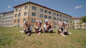 Cuatro graduados de la colegiala están mintiendo en la hierba contra el contexto de su escuela Escuela rusa metrajes
