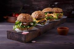 Cuatro hamburguesas hechas en casa en la tabla de madera foto de archivo