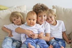 Cuatro hermanos en un sofá Fotos de archivo