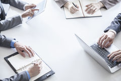 Cuatro hombres de negocios alrededor de una tabla y durante una reunión de negocios, manos solamente Imagen de archivo
