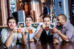 Cuatro hombres de negocios beben la cerveza y gozados el ver de la TV en el b foto de archivo