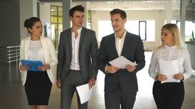 Cuatro hombres de negocios que hablan y que caminan en pasillo de la oficina almacen de video