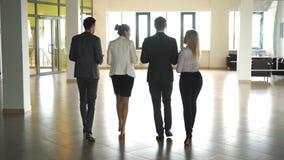 Cuatro hombres de negocios que hablan y que caminan en pasillo de la oficina metrajes