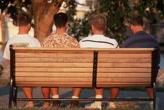 Cuatro hombres jovenes de la parte posterior en banco Fotos de archivo libres de regalías