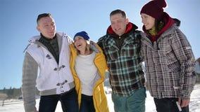 Cuatro hombres y mujeres están disfrutando del tiempo caliente del invierno que está en el campo en las montañas Grupo de amigos  almacen de video