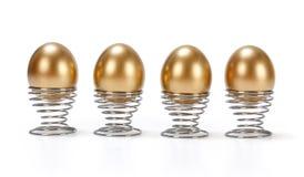 Cuatro huevos de oro en fila Imágenes de archivo libres de regalías