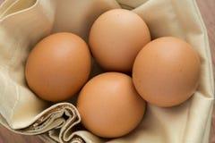 Cuatro huevos en la tela Imagenes de archivo