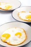 Cuatro huevos fritos en tres placas Imagen de archivo libre de regalías