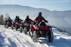 Cuatro jinetes de ATV en los coches de cuatro ruedas campo a través ATV bikes en las montañas del invierno Imágenes de archivo libres de regalías