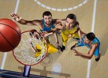 Cuatro jugadores de básquet durante refriega en arena del nasketball imagen de archivo