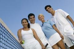 Cuatro jugadores de tenis de los dobles mezclados en la red en la opinión de ángulo bajo del retrato del campo de tenis Foto de archivo