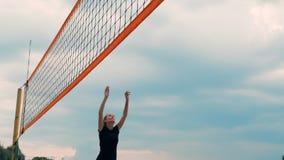 Cuatro jugadores de voleibol de las muchachas juegan en la playa en el verano que participan en el torneo en la cámara lenta en l metrajes