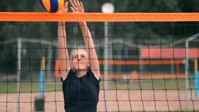 Cuatro jugadores de voleibol de las muchachas juegan en la playa en el verano que participan en el torneo en la cámara lenta en l almacen de video