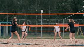 Cuatro jugadores de voleibol de las muchachas juegan en la playa en el verano que participan en el torneo en la cámara lenta en l almacen de metraje de vídeo