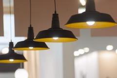 Cuatro lámparas pendientes empañaron el fondo fotos de archivo