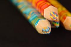 Cuatro lápices multicolores en un fondo negro llano Imagen de archivo