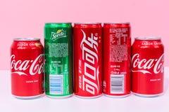 Cuatro latas de Coca-Cola y uno pueden sprite, tres latas escritas en chino fotos de archivo libres de regalías