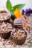 Cuatro magdalenas del chocolate en el tablero blanco con color florecen Foto de archivo