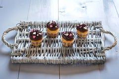 Cuatro magdalenas deliciosas del chocolate en una bandeja de mimbre Foto de archivo libre de regalías