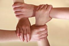 Cuatro manos de los niños que se enclavijan Imagen de archivo libre de regalías