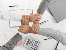 Cuatro manos junto en la unidad en businessmeeting Fotografía de archivo libre de regalías