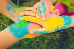 Cuatro manos pintadas en diversos colores Concepto de amor, amistad, felicidad en familia Imágenes de archivo libres de regalías
