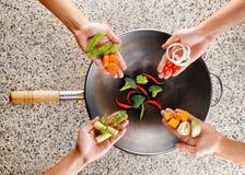 Cuatro manos ponen verduras frescas en el wok. Cocinar concepto Fotografía de archivo