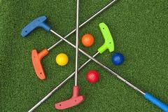 Cuatro Mini Golf Putters y bolas Imágenes de archivo libres de regalías