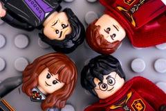 Cuatro minifigures de Lego Harry Potter - Harry Potter, Hermione Granger, Severus Snape y Oliver Wood en fondo gris imagen de archivo